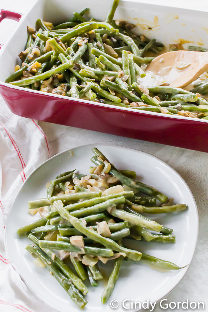 vegan green bean casserole on a white plate next to a baking dish of the casserole