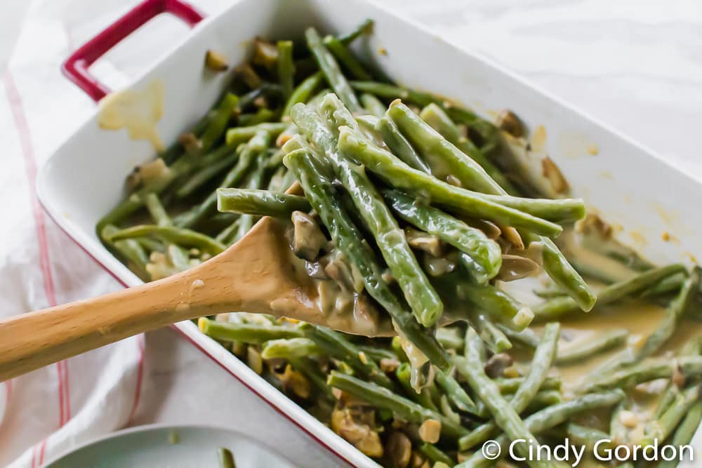 green bean casserole being served from a baking dish with a wooden spoon