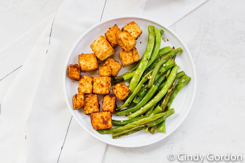 a round white plate on a marble countertop with roasted tofu and green beans