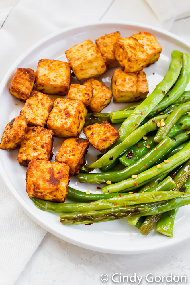 Baked tofu and seasoned green beans on a white plate on a marble countertop