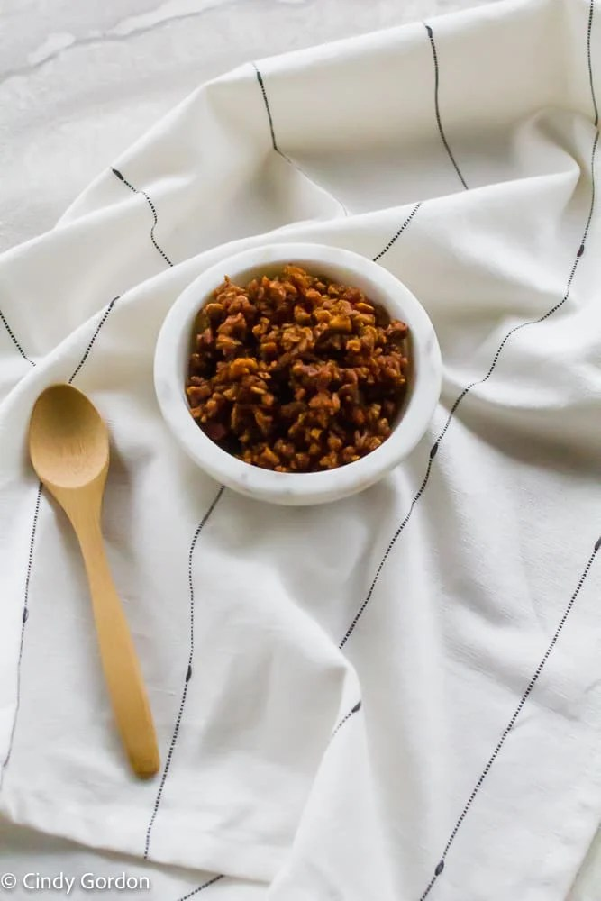 A small white bowl of bacon bits on a black and white kitchen towel with a wooden spoon