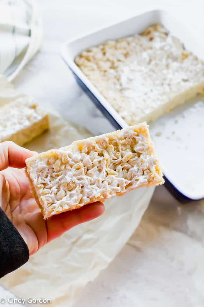 A vegan rice crispy treat in someone's hand above a baking dish