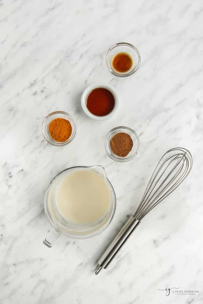 measured ingredients for turmeric latte. Ingredients are in clear and metal containers on a white marble background.