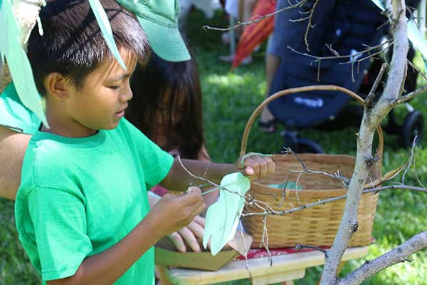 a child attaches a vision to the Blessing Tree