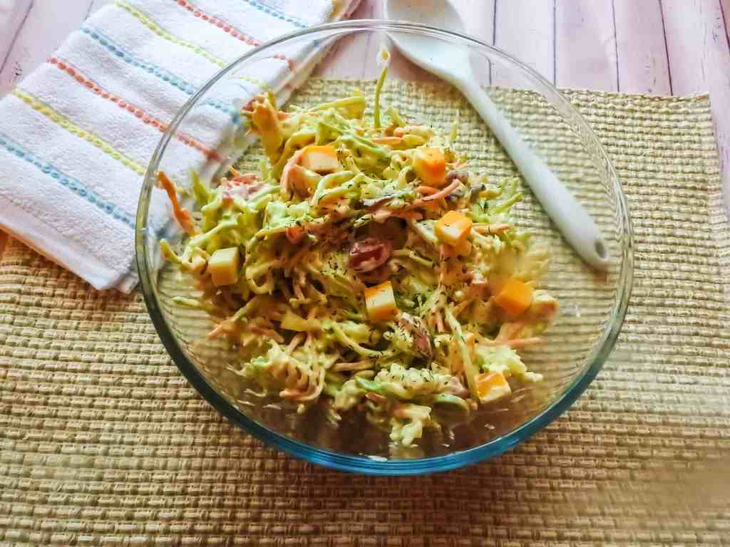 Vegetarian pasta salad in glass bowl on placemat with spoon and striped towel