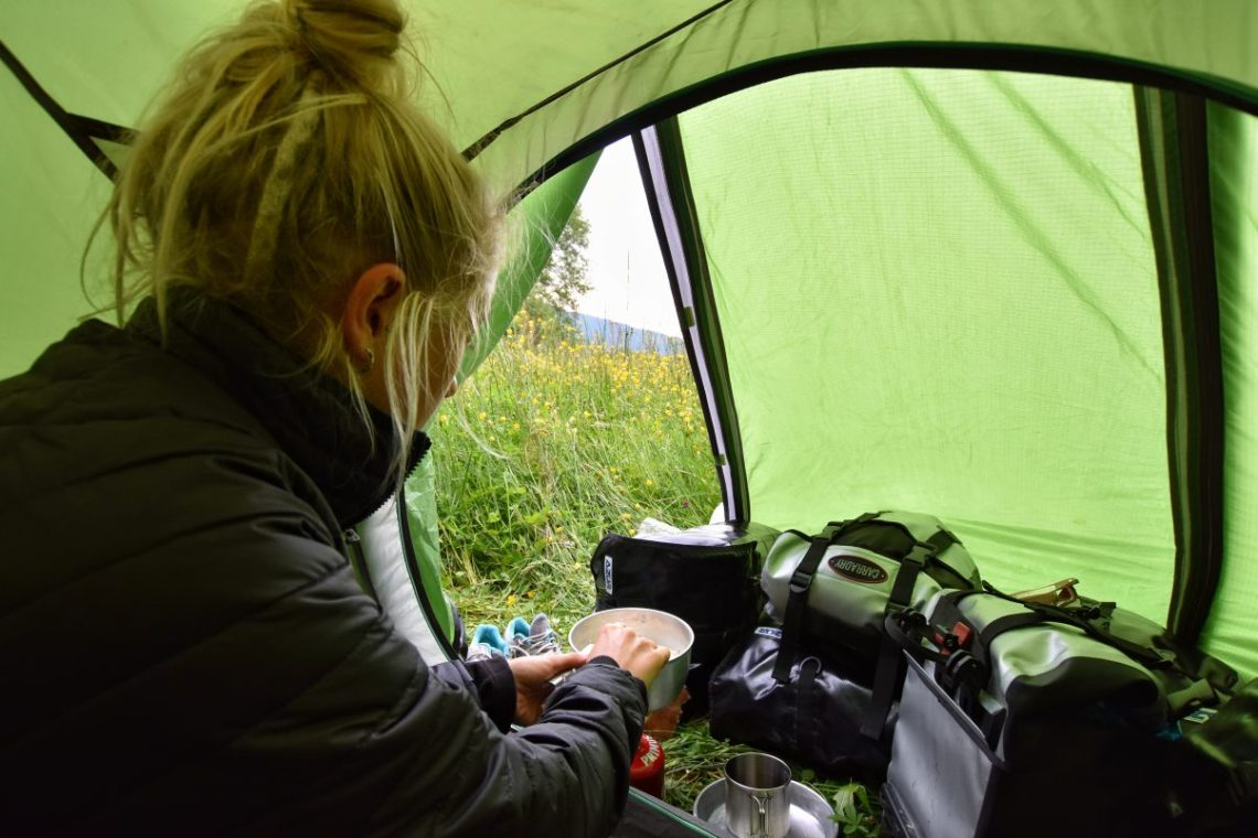 Girl cooking food in front of tent