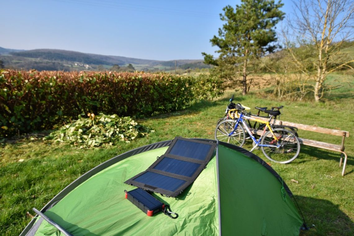 Charging battery pack from solar charger on top of tent in field