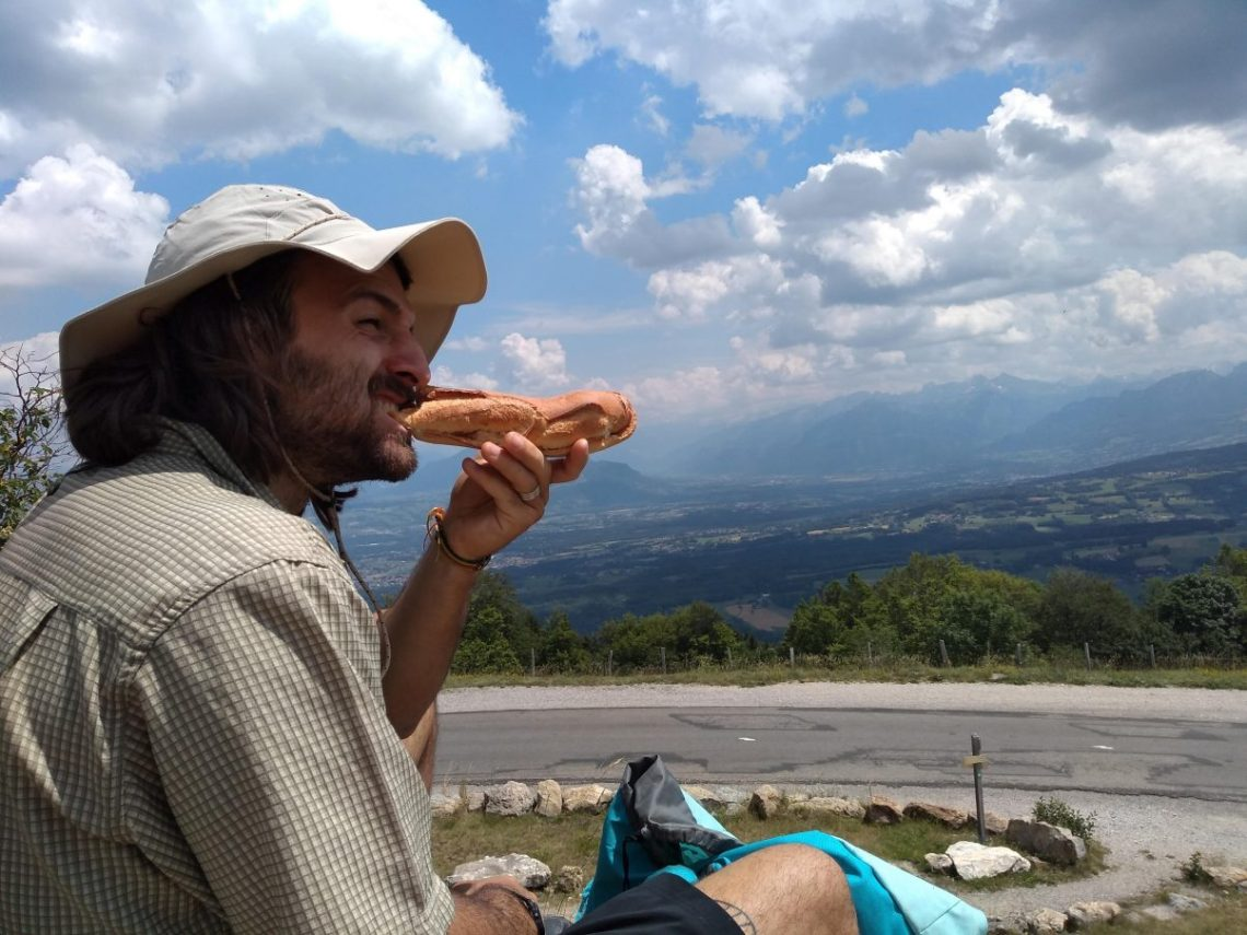 Hiking man having lunch in the sun