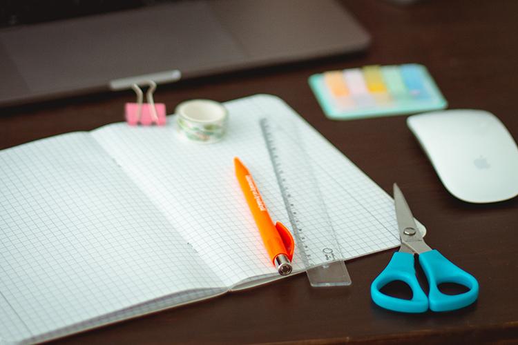 Block, penna, sax och linjal på ett bord