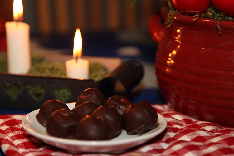 Chokladbollar på ett fat, i bakgrunden en adventsljusstake med tända ljus