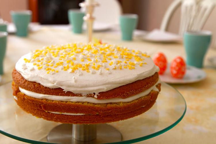 Tårta i tre lager med vit fyllning mellan, gult och vitt strössel på översta raden, ett par påskägg i bakgrunden.