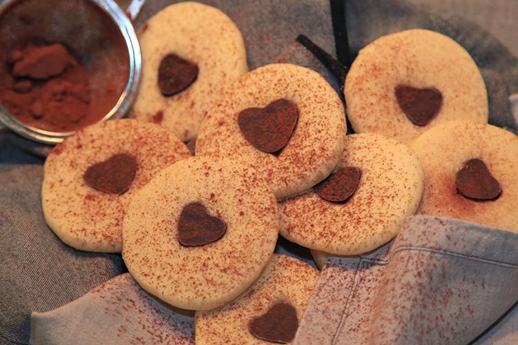 Ljusa, runda kakor med chokladhjärta i mitten, kakao pudrat över