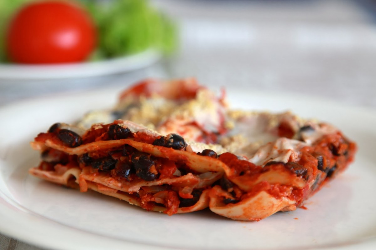 En portion lasagne på en vit tallrik