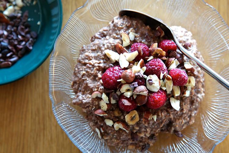 En skål med chokladfärgad gröt, toppad med hallon och hasselnötter