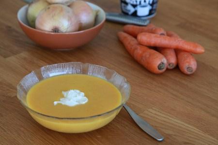 Gul morotssoppa i glasskål med sked till höger, i bakgrunden en skål med gul lök, några morötter och ett paket iFraiche
