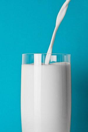 Ett glas som fylls med mjölk mot turkos bakgrund