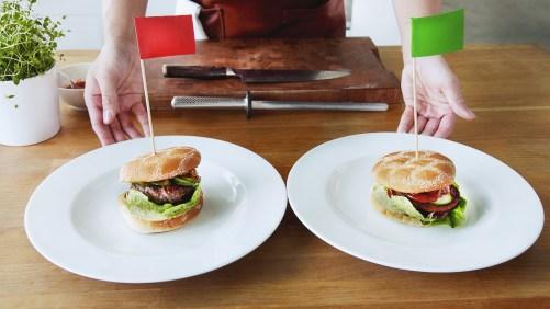 Två vita tallrikar med varsin hamburgare med bröd på. Båda likadana med sallad och grönsaker som sticker ut men ingredienserna i burgarna är olika. Den med kött har en röd flagga på träpinne instinkt i sig och den veganska en grön flagga.