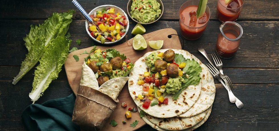 Wrapmåltid uppdukad med olika skålar med röror och Grönsaksbullar på