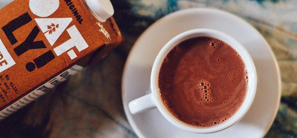 En vit kopp med fat med choklad i, brunt Oatly-paket med chokladdryck ligger till vänster