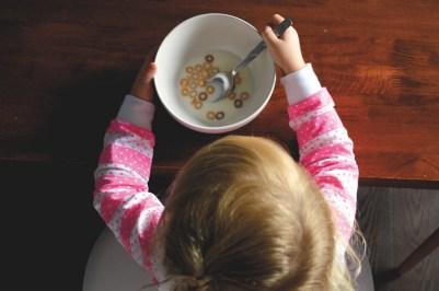 Ett barn sett uppifrån med en skål med mjölk och flingor framför sig. Håller en sked i höger hand för att äta från skålen.