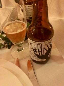 Brun ölflaska till höger om ölglas med lite öl intill tallrik och bestick på vit linneduk
