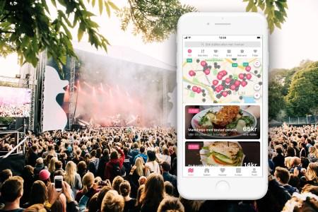 Bild på en scen med ett publikhav framför. Inklippt på bilden är en smartphone med en karta över matställen på.
