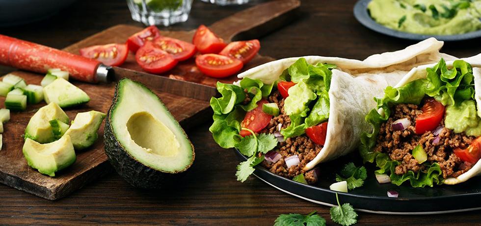 Avocado och tomat på en skärbräda, till höger två tortillabröd fyllda med grönsaker och färs