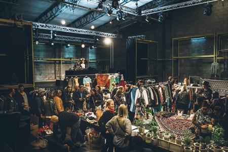 Översiktsbild över marknad med människor och klädställningar