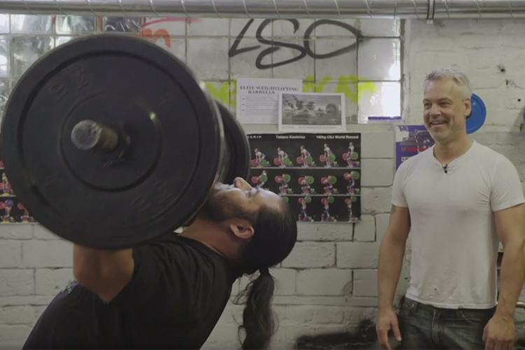 Mycket muskulös man lyfter skivstång med stor vikt, till höger en mindre man som tittar på och skrattar