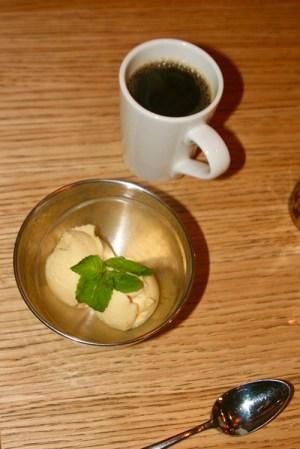 Metallskål med två kulor sorbet i gul ton samt en vit kopp med kaffe