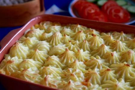 Rektangulär keramikform med spritsat mos, skivade tomat och gurka i bakgrunden