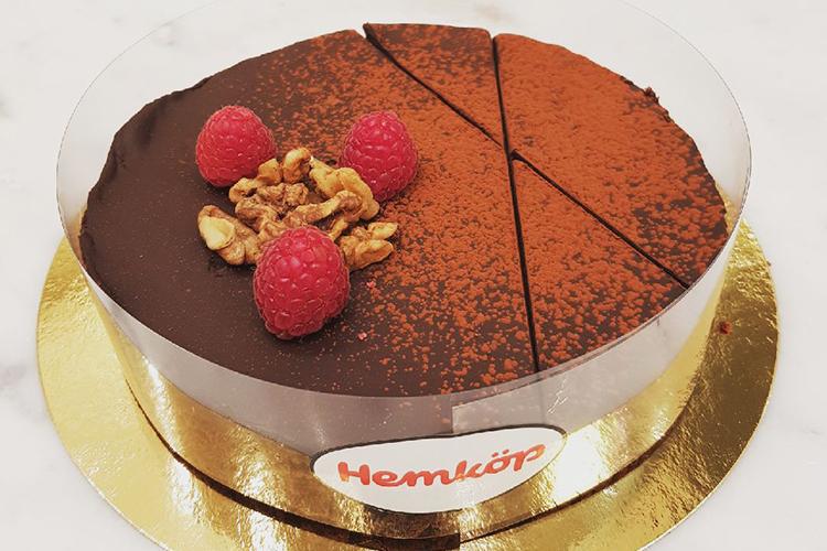 Chokladtårta sedd uppifrån på en guldplatta, garnerad med tre färska hallon