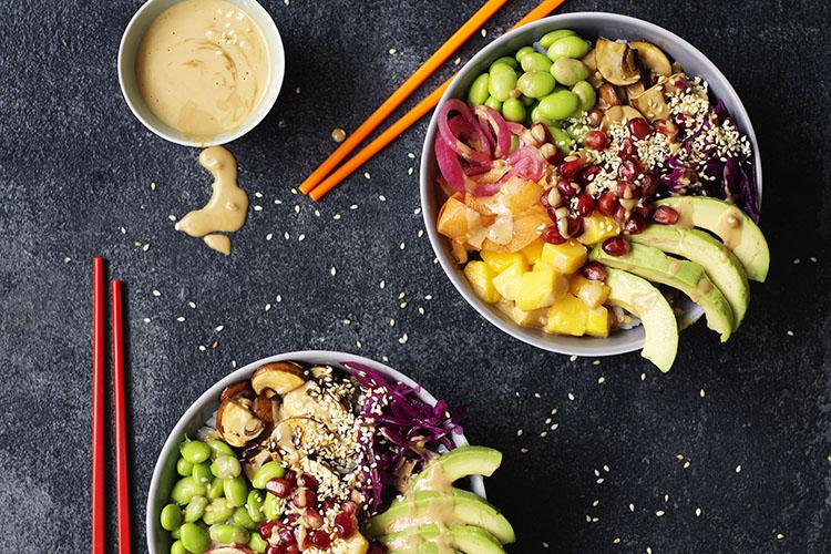 Två skålar med bönor och grönsaker i, ovanför ett par ätpinnar och en liten skål med jordnötssås