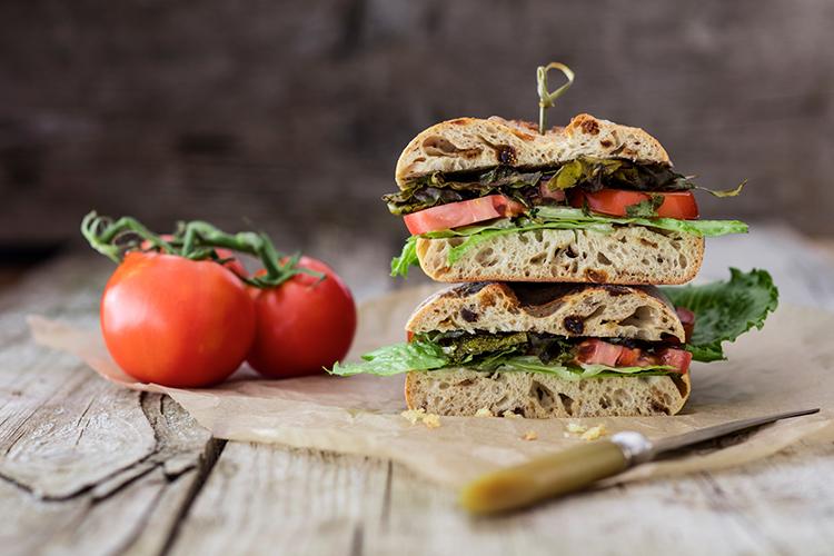 Bröd i fyra lager med tomat och baconliknande innehåll. Två tomater till vänster om smörgåsen