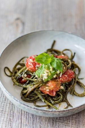 En tallrik med en tagliatellerätt, pastan är grön och gjord av alger