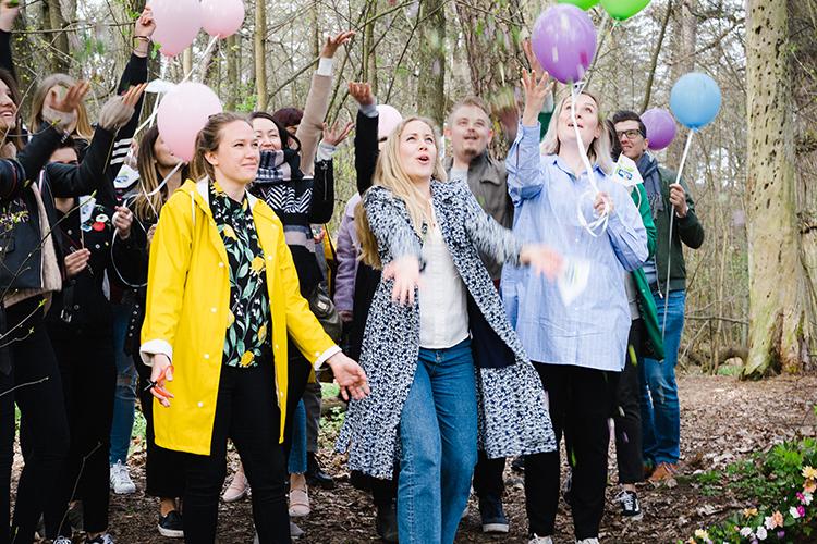 Flera personer står i en skog med ballonger och är glada, feststämning