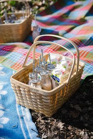 Picknickkorg på filt med flaskor med sugrör i samt tre Alproförpackningar