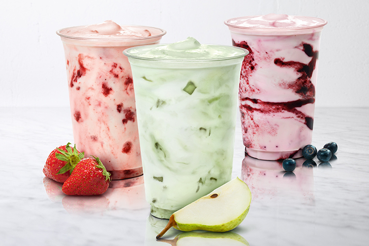 Tre plastglas med lock med milkshake i. Två jordgubbar ligger framför ett och en päronkyfta framför ett annat