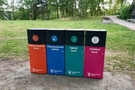 Fyra återvinningssopkorgar bredvid varandra, olika färger för varje material; plast, papper, färgat och ofärgat glas