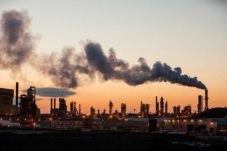 Tjärsandsuppgraderingsanläggningen vid Syncrude-mine i solnedgång