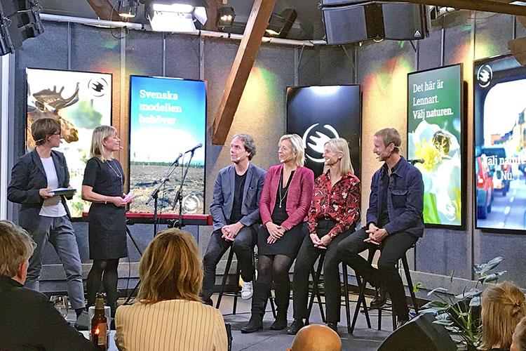 Fem personer på en scen, två står till vänster, fyra personer sitter på höga stolar till höger