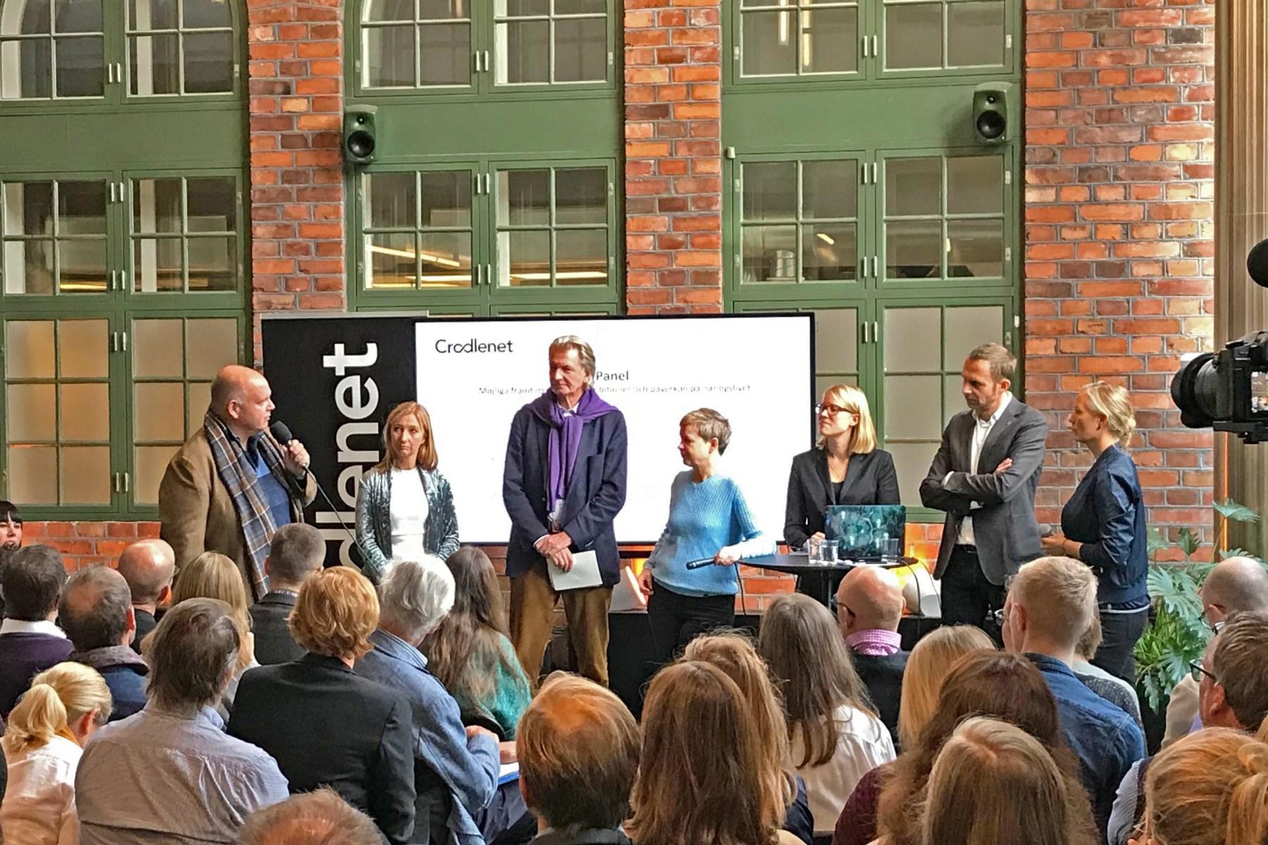 Sju personer står framför en publik