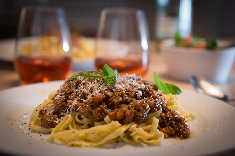 Tallrik med spaghetti och bolognese sedd från sidan, glas med röd dricka i bakgrunden