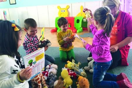 Barn i en ring på en matta med leksaker i mitten