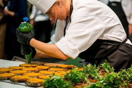 Kvinna i kockkläder spritsar hummus på smörgåsar