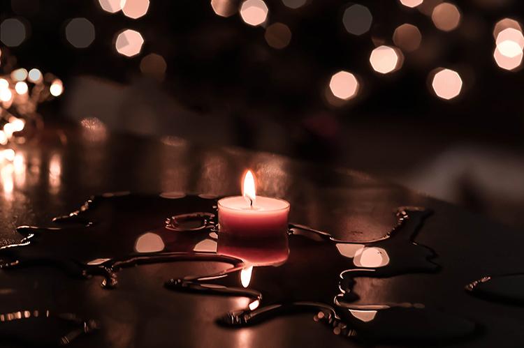 Ett tänt värmeljus på en mörk yta med vätska som reflekteras i ljuset