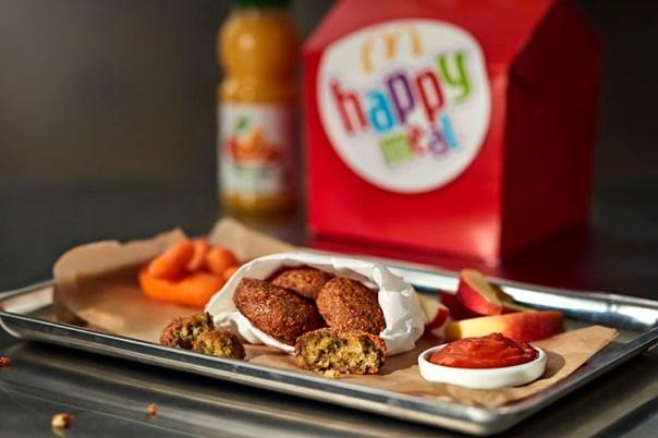 En bricka med falafel, skål med ketchup och morötter, i bakgrunden förpackning till Happy Meal