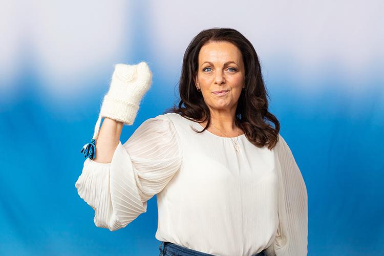 Mörkhårig kvinna mot blå bakgrund håller upp knuten näve med vit lovikavante