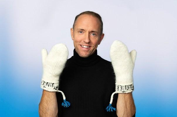 En man mot ljusblå bakgrund håller upp båda händerna med vita lovikavantar på