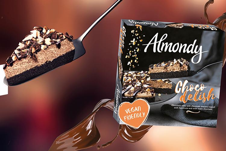 Tårtspade med en bit chokladtårta på, till vänster en förpackning med en bild på samma chokladtårta